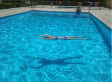 Woman Swimming in clean pool in Little Rock Arkansas by the best pool cleaners near me