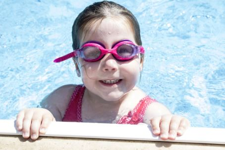 Young girl with goggles smiling at the camera and holding onto the side in a clean pool in Benton Arkansas