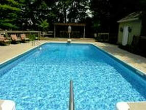 Picture of a clean blue rectangular pool in Little Rock Ar looking from the shallow end toward the diving board end