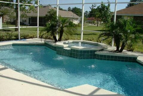 Nice Clean pool surrounded by a mosquito net fence, with a hot tub in the middle of the pool on the side deck
