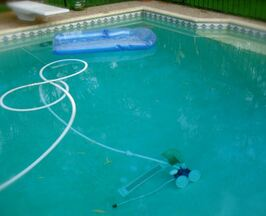 Picture of a pool vacuum Polaris running on the bottom of a somewhat dirty pool with the hose floating across the top of the water